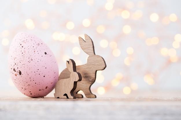 Decorações de páscoa, coelhos de madeira e ovo rosa Foto Premium