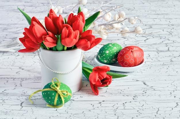 Decorações de páscoa, tulipas e ovos coloridos, nas cores vermelhas e verdes Foto Premium