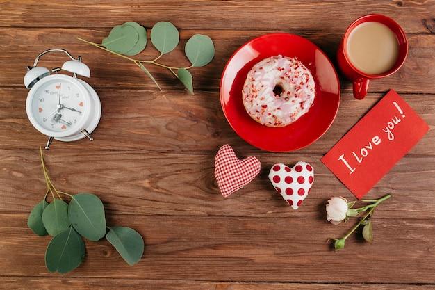 Decorações do dia dos namorados perto de pequeno-almoço com donut Foto gratuita