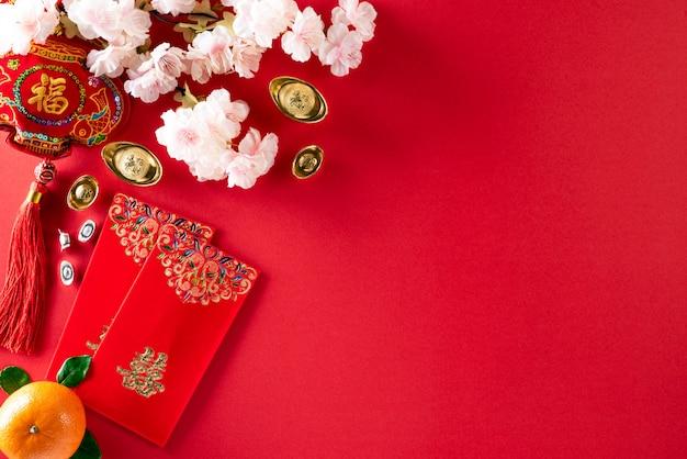Decorações do festival do ano novo chinês pow ou pacote vermelho, lingotes de laranja e ouro ou caroço de ouro no vermelho Foto Premium