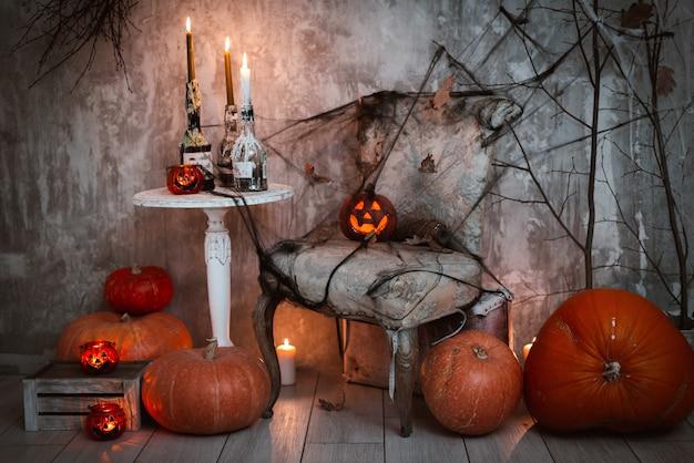 Decorações para a festa de halloween. uma composição assustadora com abóbora de jack e velas acesas, teias de aranha e vassoura de bruxa em uma parede de concreto Foto Premium