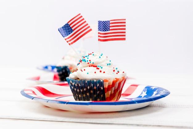 Decorado com pequenas bandeiras dos eua e bolo de cobertura na placa Foto gratuita