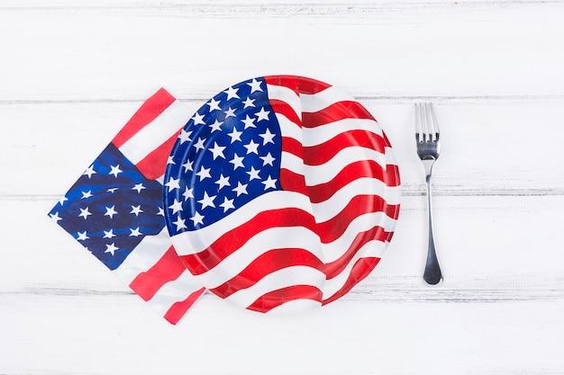 Decorado com placa de bandeira da américa, guardanapo e garfo na mesa Foto gratuita