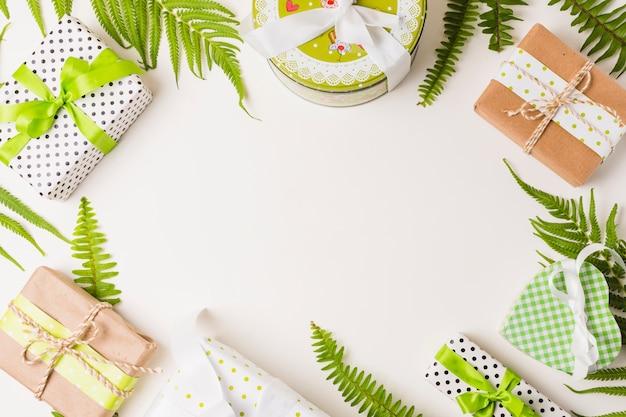 Decorativas caixas de presente e folhas galho arranjado no fundo branco Foto gratuita