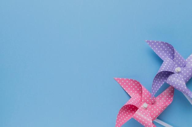 Decorativo dois cata-vento pontilhado de polca no pano de fundo azul Foto gratuita