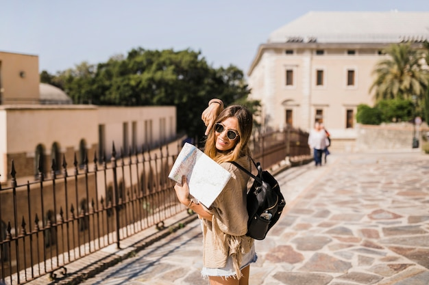 Dedo apontando elegante feminino turista no mapa Foto gratuita