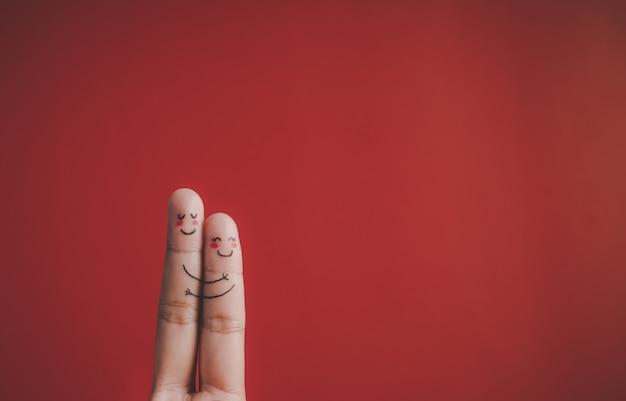 Dedo com emoção em fundo vermelho Foto gratuita