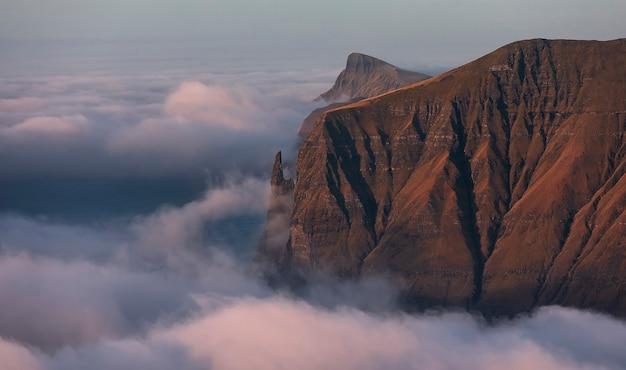 Dedo da bruxa do rock ao amanhecer. nuvens cobriam o oceano atlântico. ilhas faroé, europa. Foto Premium