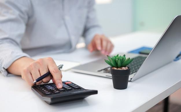Dedo de homem empregado pressione na calculadora Foto Premium