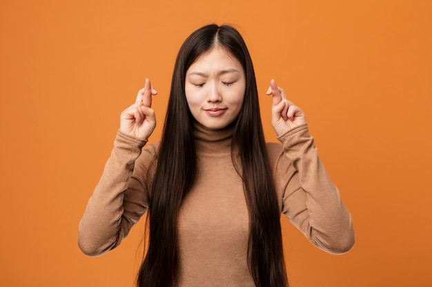 Dedos bonitos do cruzamento da jovem mulher chinesa por ter sorte Foto Premium