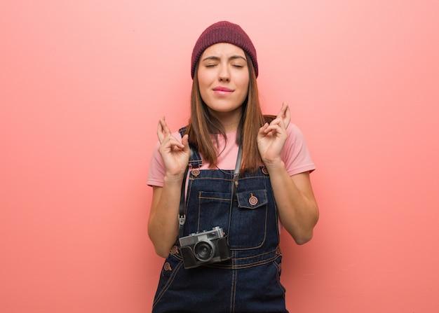 Dedos de cruzamento bonito jovem fotógrafo mulher por ter sorte Foto Premium