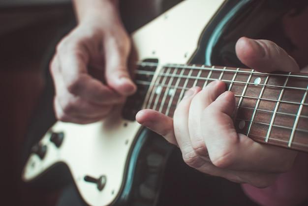 Dedos formando um acorde no braço de uma guitarra Foto Premium