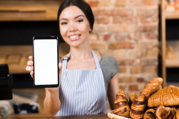 Defocused feminino padeiro em pé atrás do balcão mostrando o telefone móvel Foto gratuita