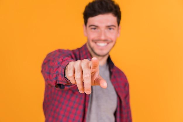 Defocussed jovem apontando o dedo em direção à câmera contra um fundo colorido Foto gratuita