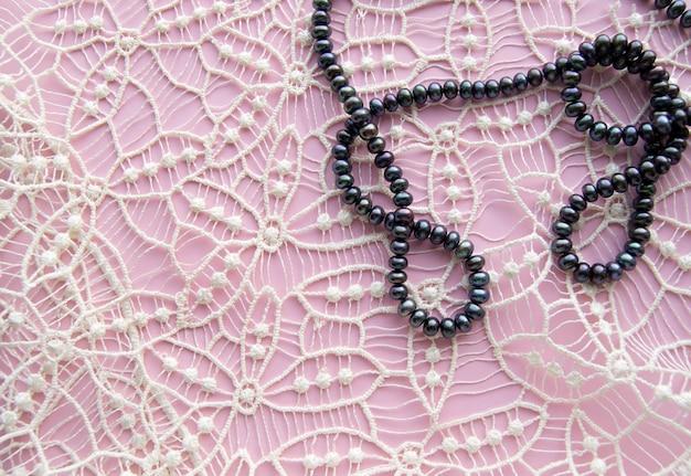 Deite fundo liso rosa e as lindas rendas, brilhantes colar de pérolas negras e pulseira elegante. Foto Premium