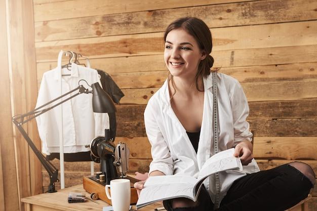 Deixe-me mostrar meu novo projeto. feliz criativa criativa alfaiate sentado na mesa e segurando os esquemas de costura, conversando com uma colega de trabalho e planejando como costurar roupas novas para sua oficina Foto gratuita