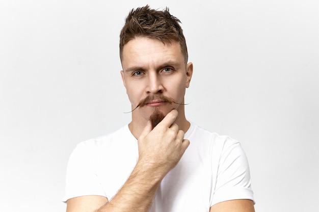 Deixe-me pensar. pensativo pensativo jovem homem branco com bigode elegante tocando sua barba cavanhaque enquanto pondera, olhando profundamente em pensamentos. linguagem corporal e expressões faciais humanas Foto gratuita