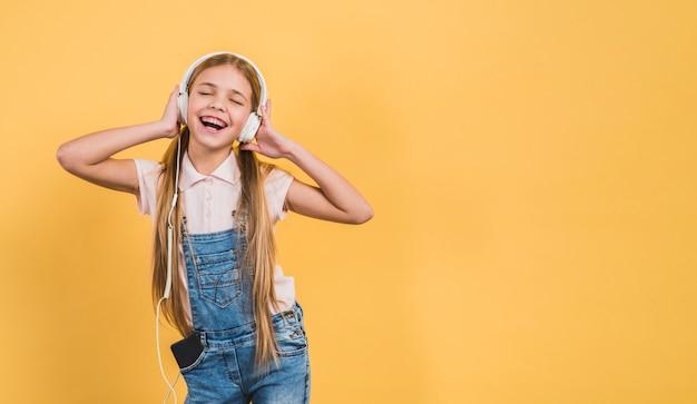 Deleite menina desfrutar ouvindo a música no fone de ouvido contra o pano de fundo amarelo Foto gratuita