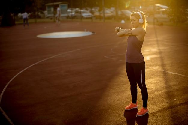 Delgado apto mulher loira fazendo alongamento antes de treino Foto Premium