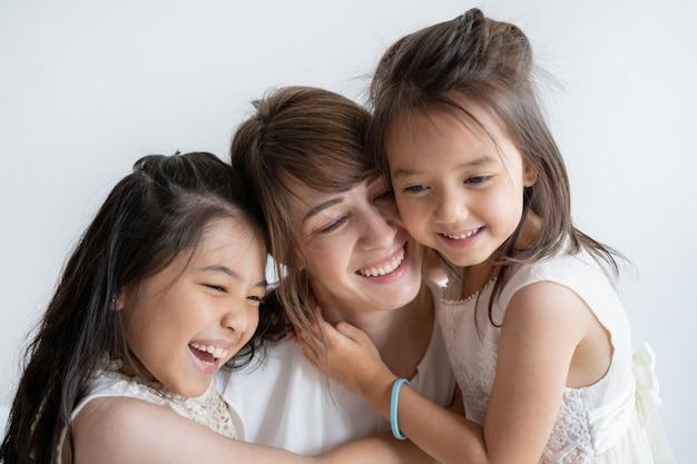 Delicada mãe caucasiana e filhas rindo e abraçando Foto gratuita