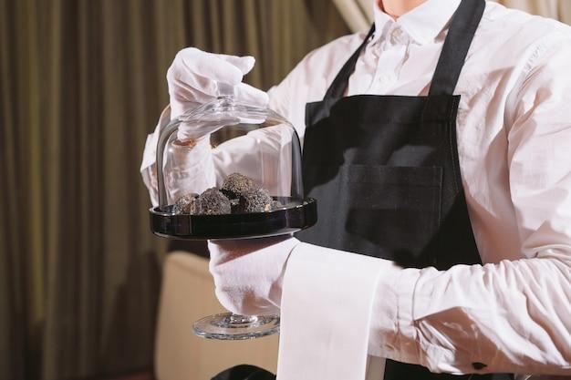 Delicadeza do chef do restaurante. trufa comida vegetariana cogumelo. conceito de refeição de serviço de garçom Foto Premium