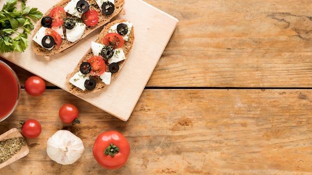 Deliciosa bruschetta na tábua de madeira e ingrediente sobre a mesa de madeira Foto gratuita