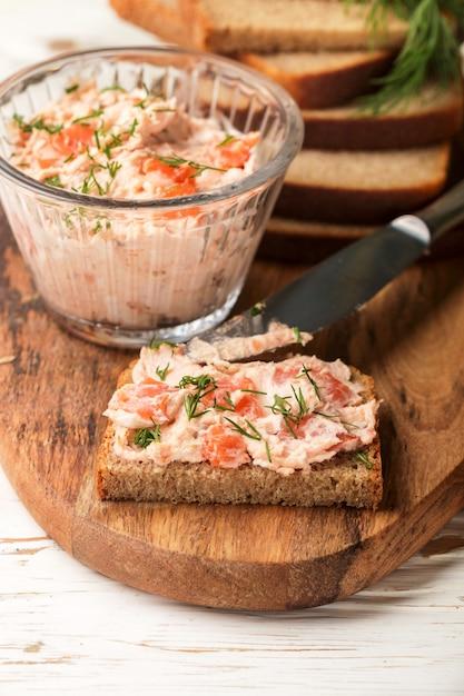 Deliciosa mousse, riyet, patê, molho de salmão defumado (truta), cream cheese, endro e rábano em fatias de pão de centeio Foto Premium