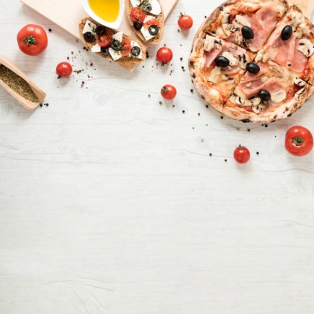 Deliciosa pizza com ingrediente saudável em fundo branco de madeira Foto gratuita
