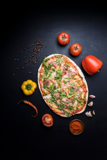 Deliciosa pizza com ingredientes e especiarias no papel de parede Foto gratuita