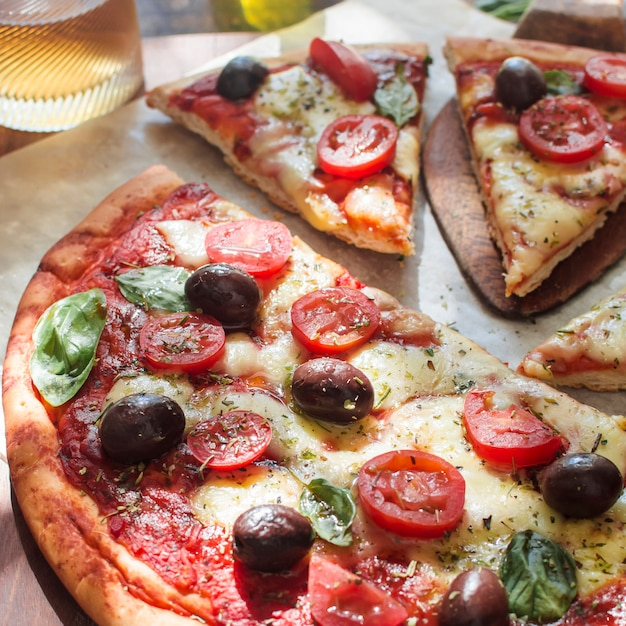 Deliciosa pizza com queijo e fatias de tomate cereja na mesa de madeira Foto gratuita