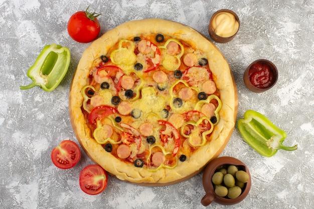 Deliciosa pizza de queijo com azeitonas, salsichas e tomates na mesa cinza fast-food de massa italiana refeição Foto gratuita