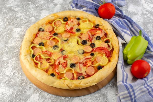 Deliciosa pizza de queijo com azeitonas, salsichas e tomates na mesa leve fast-food comida italiana massa Foto gratuita