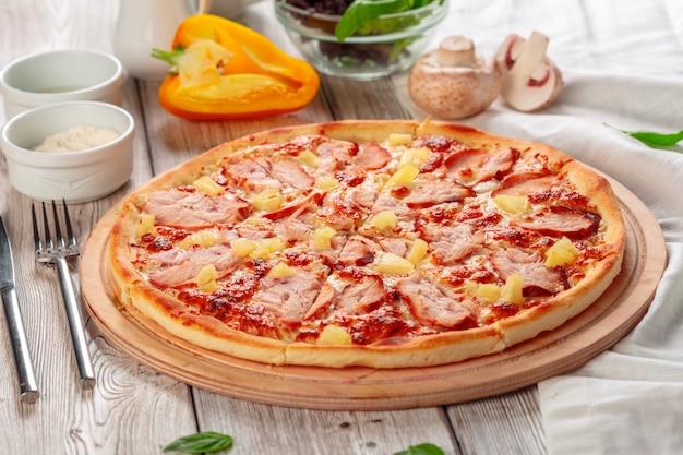 Deliciosa pizza fresca servida na mesa de madeira Foto Premium