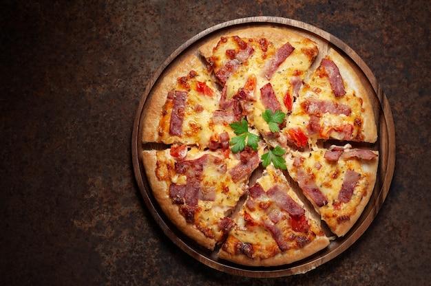 Deliciosa pizza italiana fatiado presunto, bacon e queijo com ingredientes alimentares na cozinha velha Foto Premium