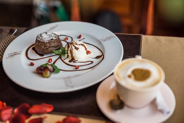 Deliciosa sobremesa de chocolate fresco e copo de bebida no restaurante Foto gratuita
