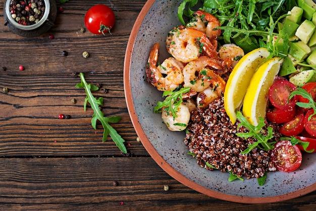 Deliciosa tigela de buda saudável com camarões, tomate, abacate, quinoa, limão e rúcula na mesa de madeira. comida saudável. vista do topo. postura plana. Foto gratuita
