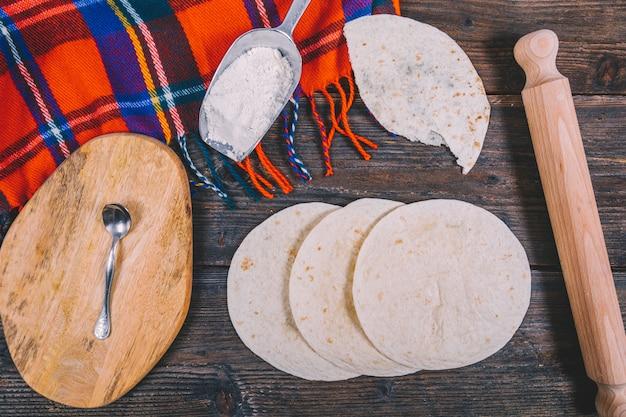 Deliciosa tortilla mexicana de trigo; rolo de madeira; colher; pano; farinha e tábua de cortar na mesa de madeira Foto gratuita