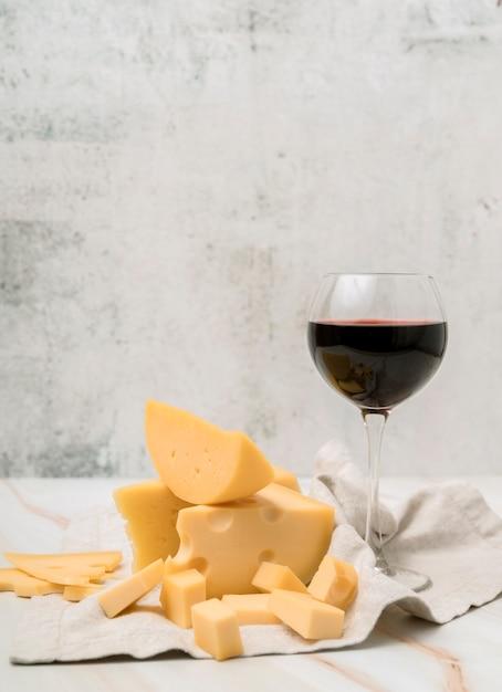 Deliciosa variedade de queijo com copo de vinho tinto Foto gratuita