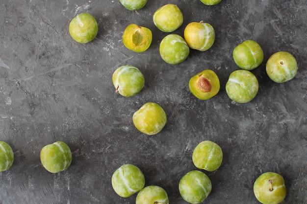 Deliciosas ameixas verdes maduras greengages fundo de concreto texturizado preto Foto Premium