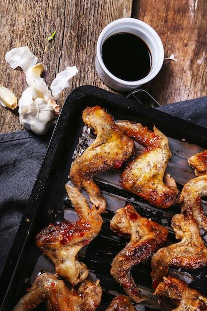 Deliciosas asas de frango na mesa de madeira Foto gratuita
