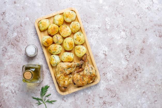 Deliciosas batatas jovens assadas com endro e frango, vista superior Foto gratuita