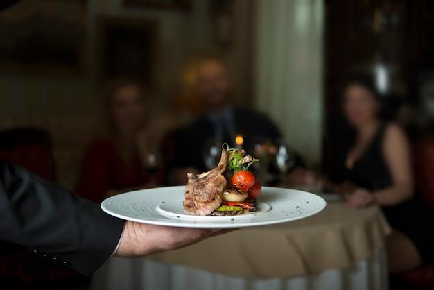 Deliciosas costelas de cordeiro grelhado, servidas com tomate grelhado e decoradas com rabanete Foto Premium