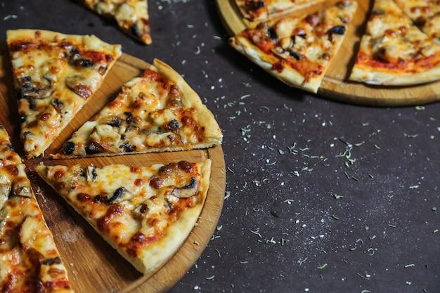 Deliciosas pizzas com frango, cogumelos e queijo Foto gratuita
