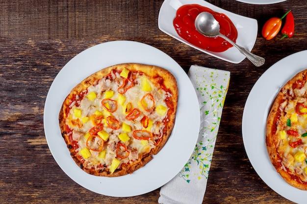 Deliciosas pizzas italianas servidas na mesa de madeira com ingredientes tiro de cima Foto Premium
