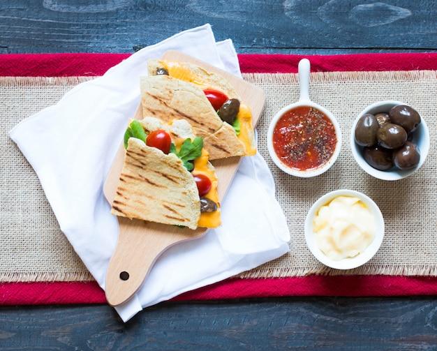 Deliciosas quesadillas de legumes com tomate, azeitona, queijo e cheddar Foto Premium