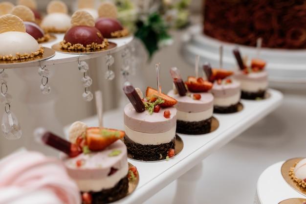 Deliciosas sobremesas mousse, decoradas com morangos no bar de doces para banquetes Foto gratuita
