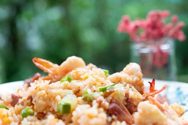 Delicioso arroz frito tailandês com camarão na mesa de madeira com vaso beauitful Foto Premium