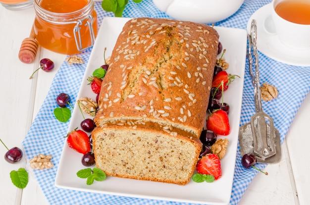 Delicioso bolo caseiro com nozes e sementes de girassol. servido com frutas frescas e mel. Foto Premium