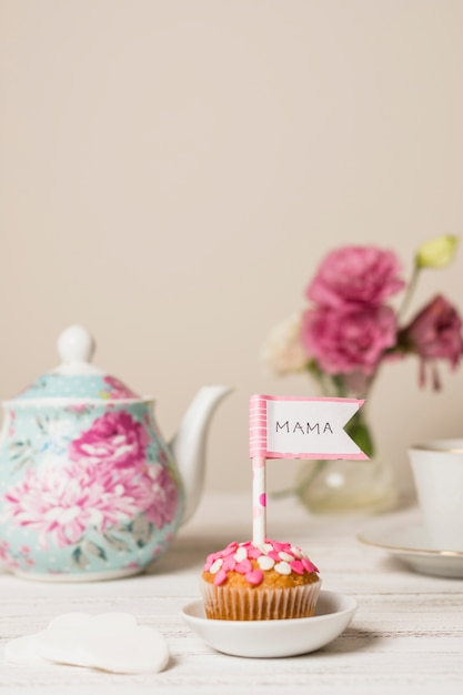 Delicioso bolo com bandeira decorativa com o título de mamãe perto de bule e flores Foto gratuita