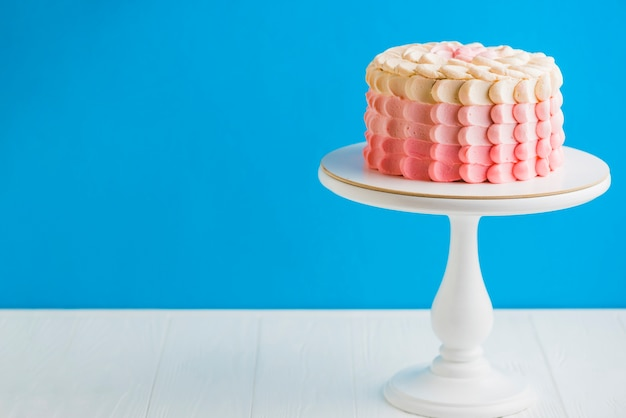 Delicioso bolo de aniversário com cakestand na frente da parede azul Foto gratuita